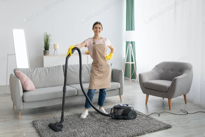 Professional cleaning service. Positive young lady in apron and rubber gloves vacuuming living room