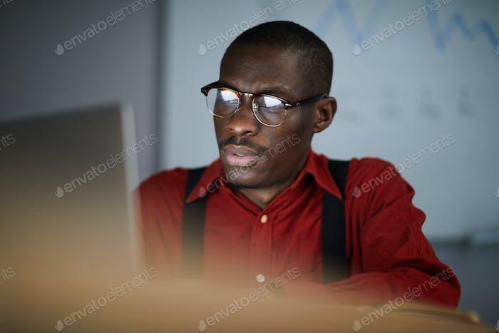 African Businessman Using Laptop in Dark Office