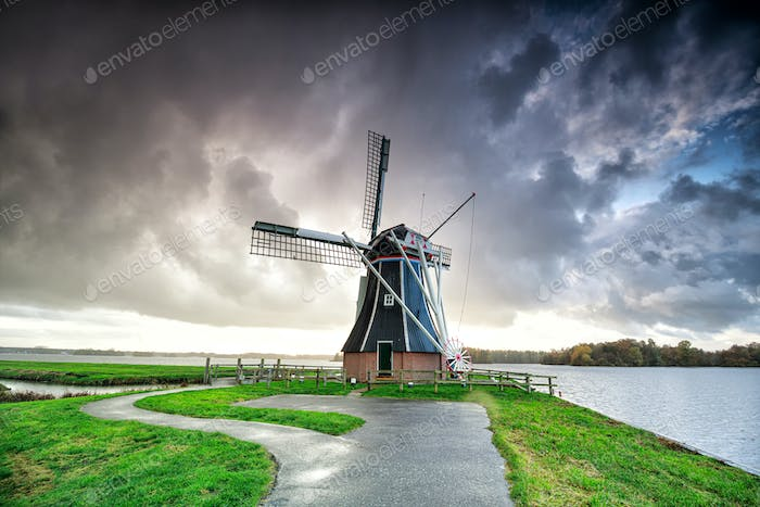 dark dramatic rainy cloud over Dutch windmill