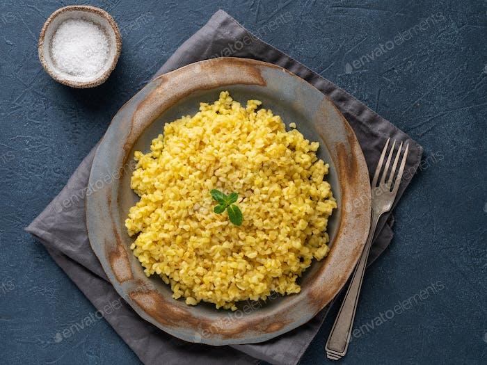 Bulgur wheat. Boiled bulghur cereal in plate on dark blue stone table. Healthy vegetarian