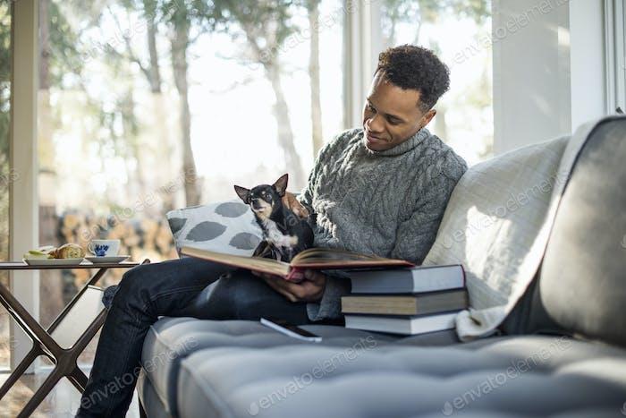 Hombre con un jersey gris de cuello redondo sentado en un sofá con un perro en su regazo, mirando un libro.