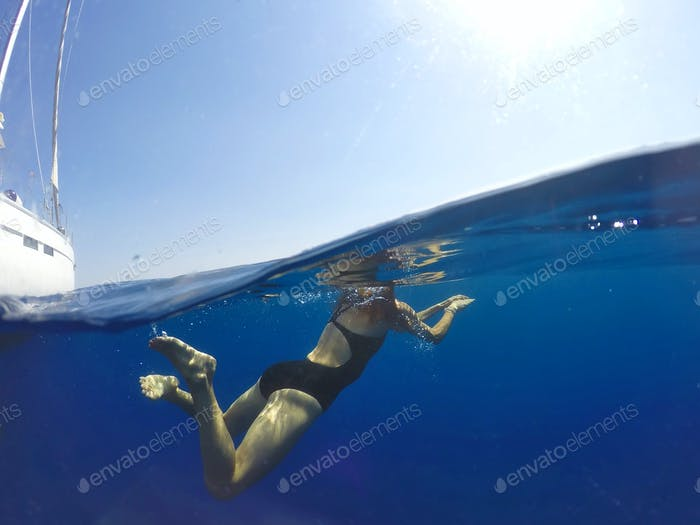 Beautiful girl swiming near the yacht. Underwater photo