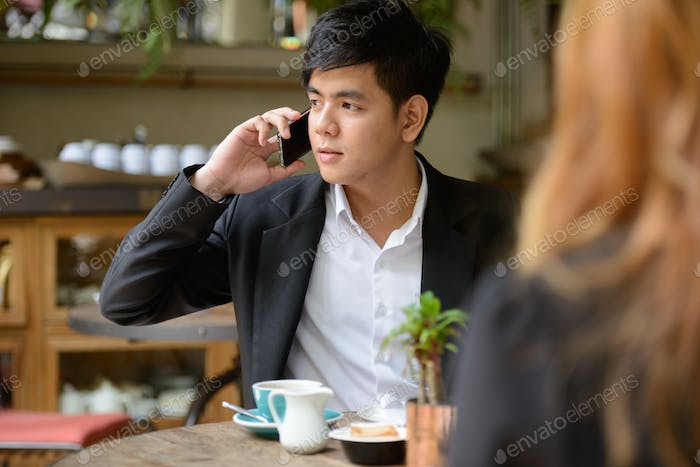 Young Asian business couple together at the coffee shop with man using phone