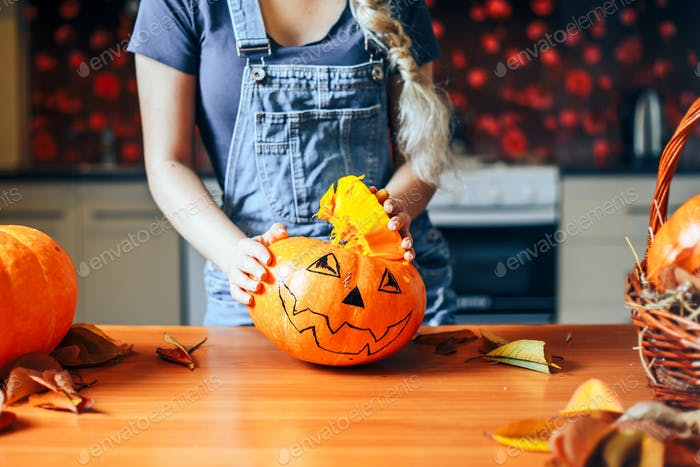 Young girl carving a pumpkin at Halloween