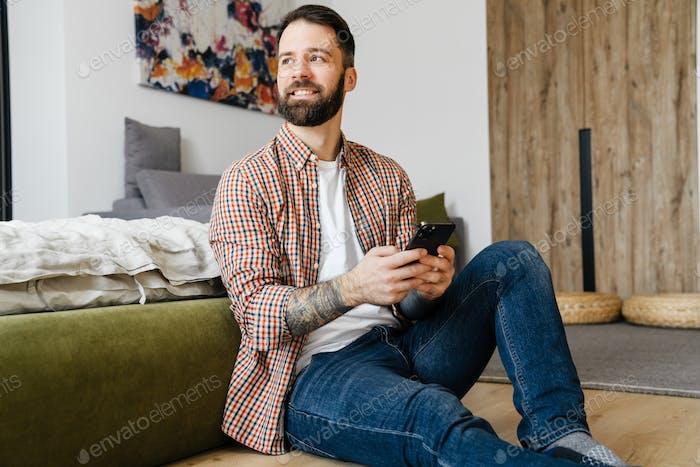 Smiling mid aged brunette bearded man holding mobile