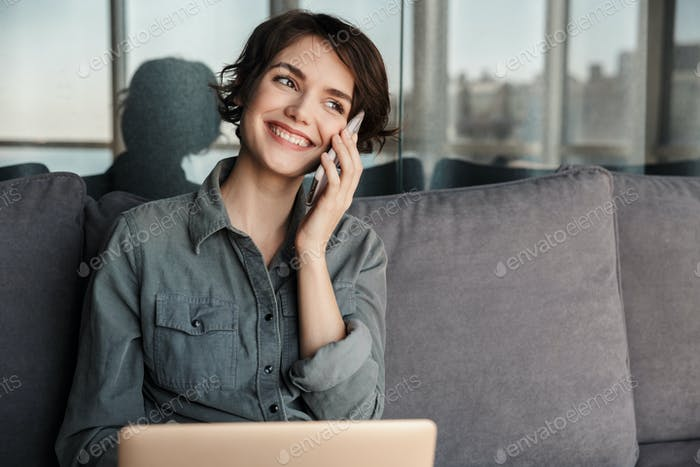 Image of brunette smiling woman using laptop and talking on cellphone