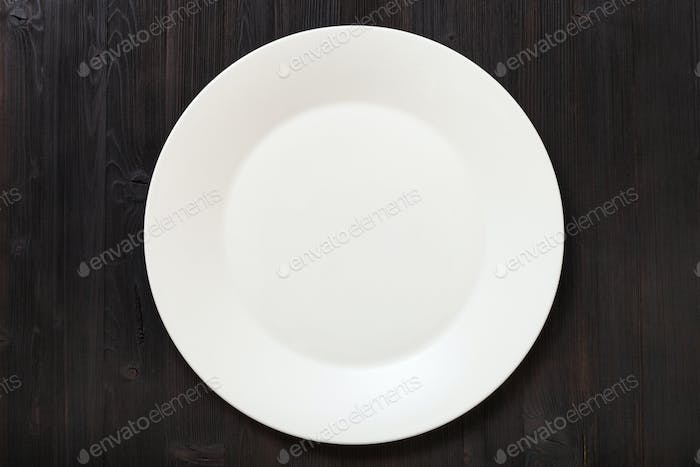 top view of white plate on dark brown table