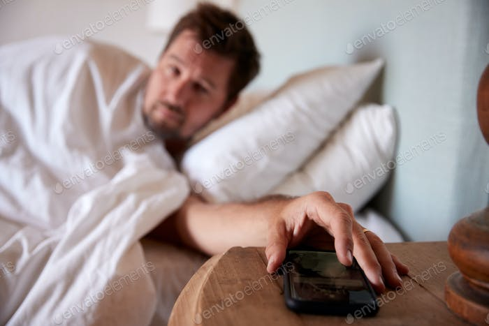 Mid adult man lying in bed, reaching out to smartphone on the bedside table in the foreground