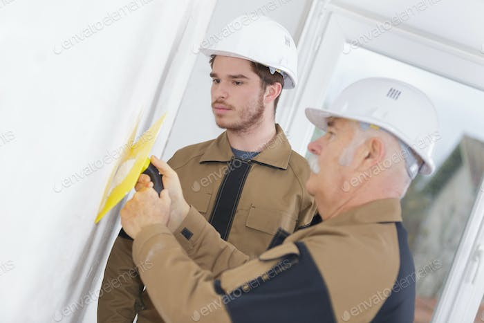 Apprentice watching teacher using trowel on wall