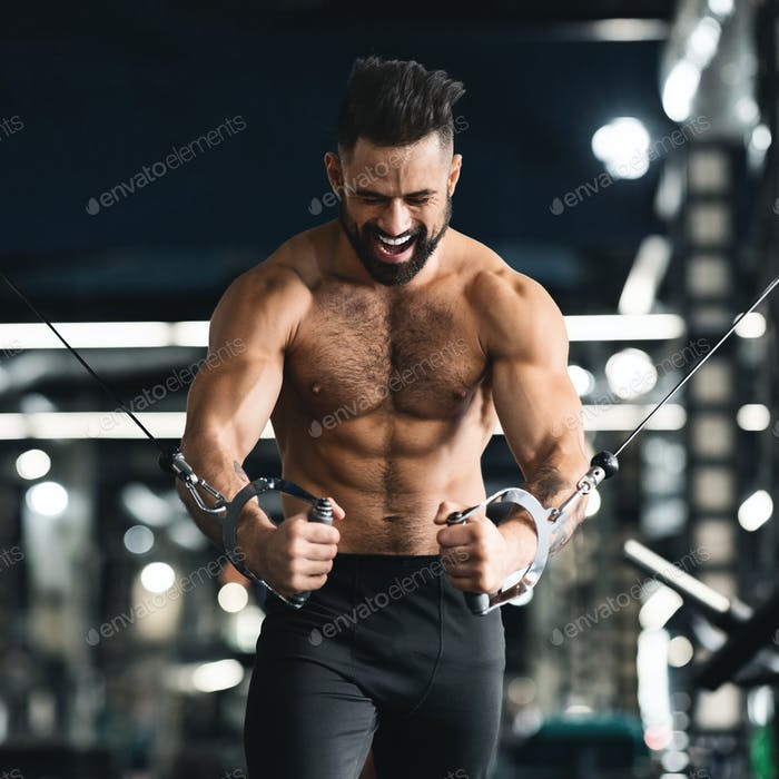 Strong muscular man training with block exerciser in gym