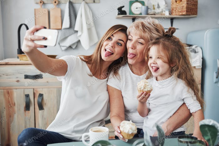 Shows tongues. Mother, grandmother and daughter having good time in the kitchen