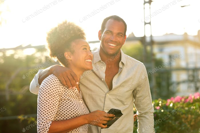 happy couple standing outside with woman holding phone