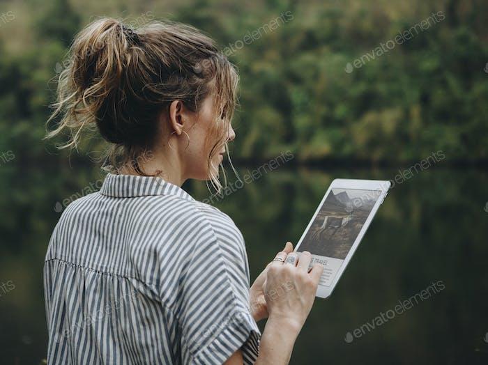 Frau allein in der Natur mit einer digitalen Tablet-Internetverbindung und Reisekonzept