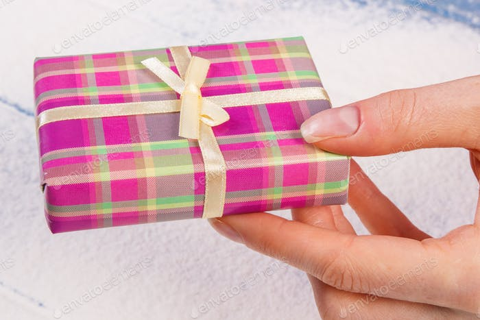 Hand of woman with gift for Christmas or other celebration