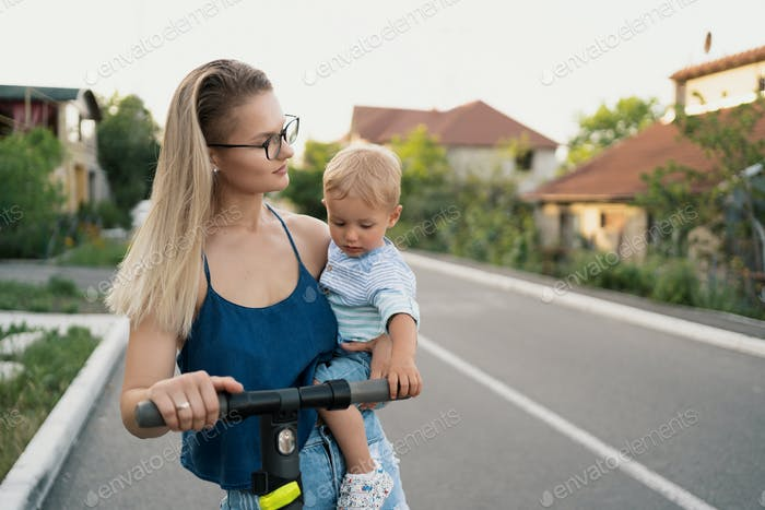 Mother and son riding an electric scooter