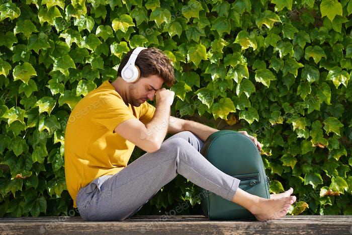 Junge Student sitzen draußen besorgt über seine Prüfungen