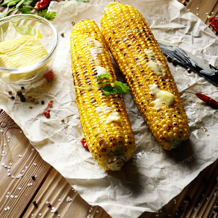 Top view of kitchen table with grilled sweet corn cob under melt
