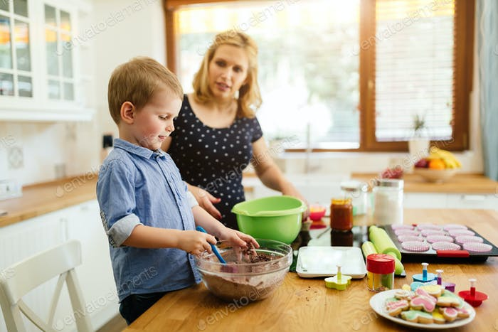 Child helping mother make muffins