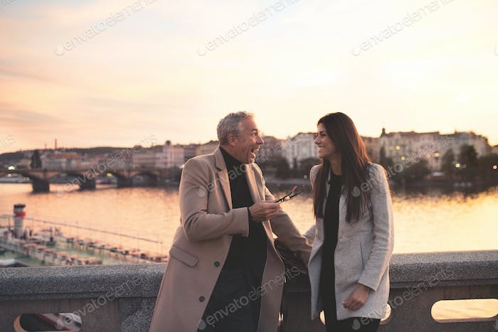 Excited man and woman business partners standing by a river in city at dusk.