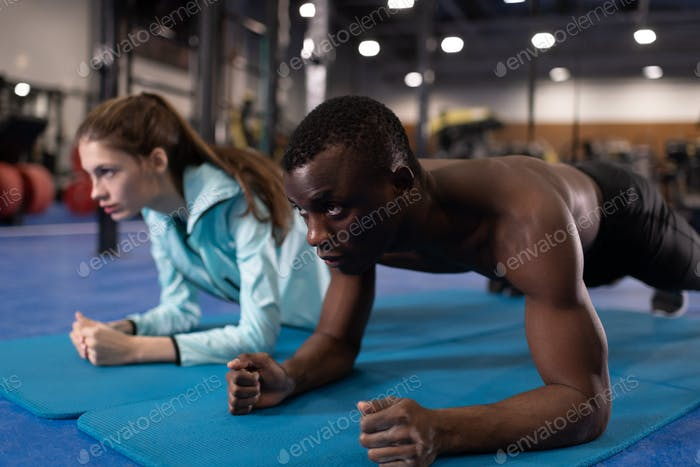 Sportive man and woman doing plank exercise in gym