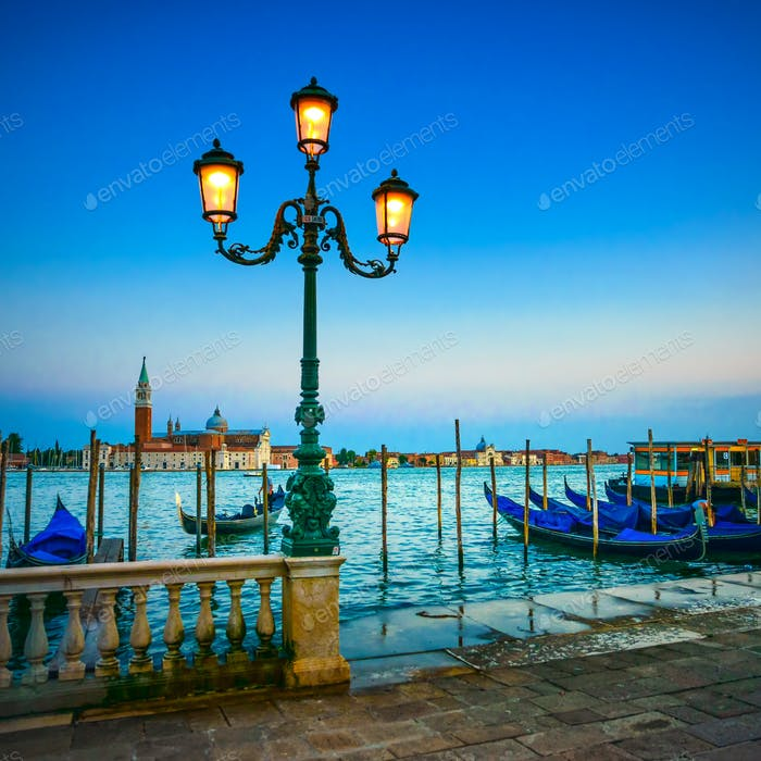 Venice, street lamp and gondolas or gondole on sunset and church