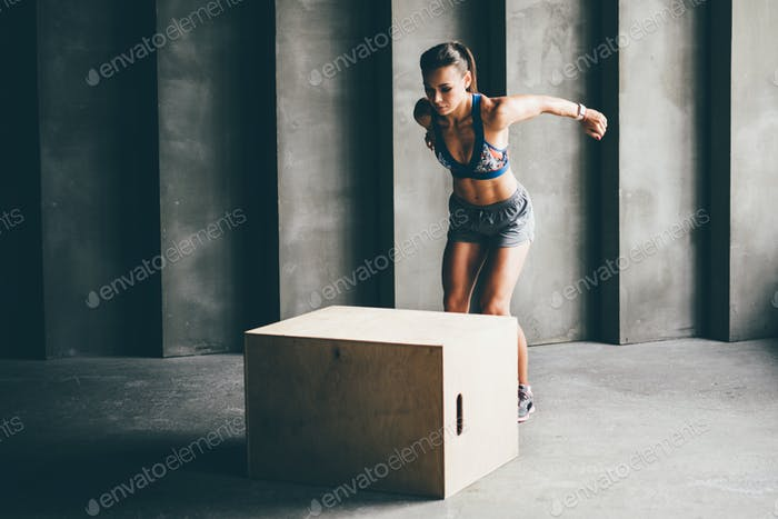 Fitness woman jumping on box while training at the gym,