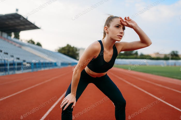 Tired female jogger, training on stadium
