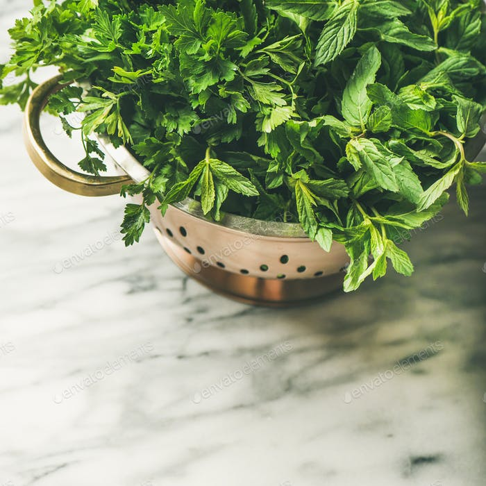 Bunch of fresh garden herbs in brass colander, square crop