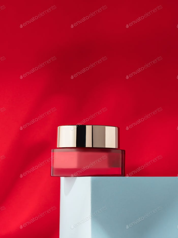 Beauty cream jar on blue podium on red with shadow