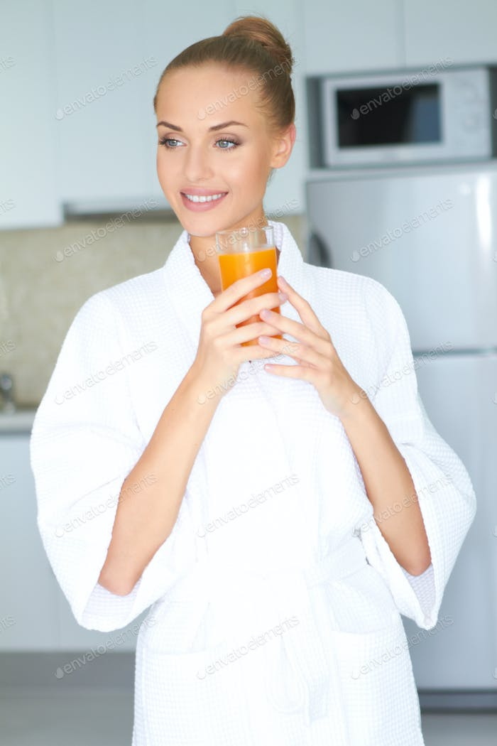 Stylish woman drinking healthy orange juice