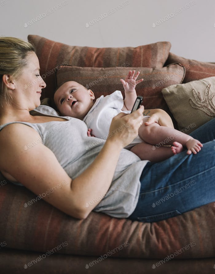 A woman lying on a sofa holding a baby girl, and holding a smart phone in one hand.