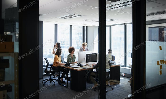 Creative business team working together in a casual office, seen through glass wall