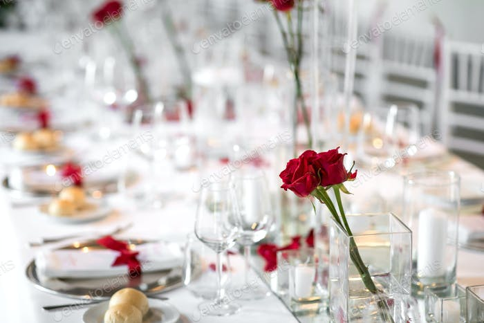 Formal dinner table setting with red roses