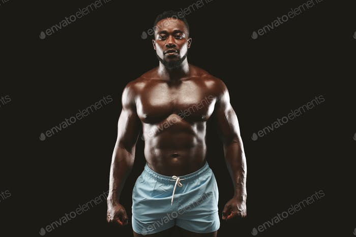 Strong athletic black man showing naked muscular body
