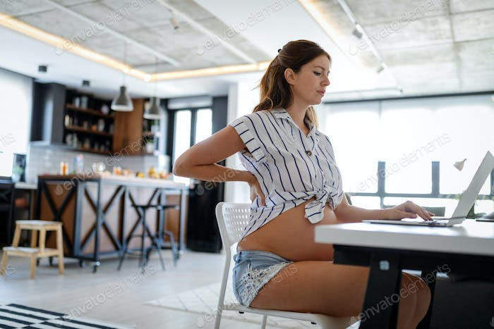 Pregnant woman working from home. Career and pregnancy concept