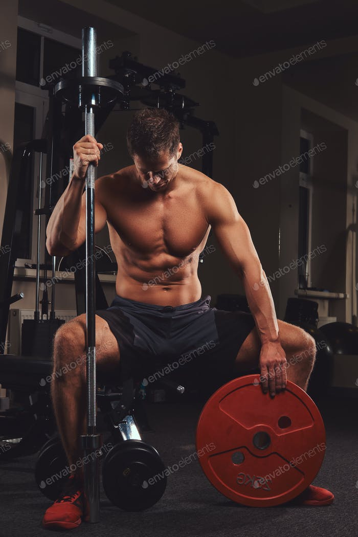 Muscular shirtless athlete holds barbell disc while sits on a bench in the gym.