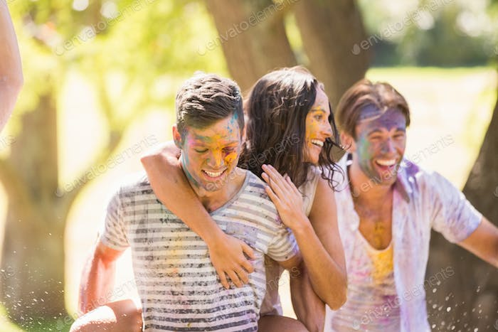 Young friends having fun with powder paint on a sunny day