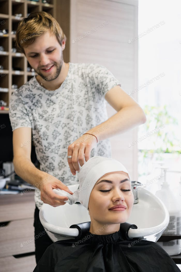 Charming young woman smiling happily while professional male hairstylist preparing her hair for the