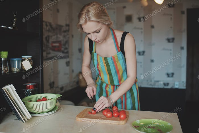 Young woman slicing tomatoes