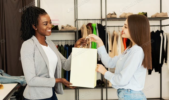 Sales Assistant Giving Package With Clothes To Buyer In Boutique