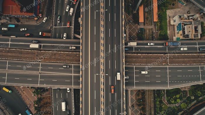 Top down cross traffic highway with cars, trucks aerial. Urban transportation at bridge road at city