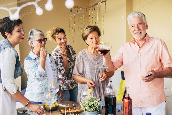 happy group of cheerful caucasian man and women mixed ages having fun together during lunch