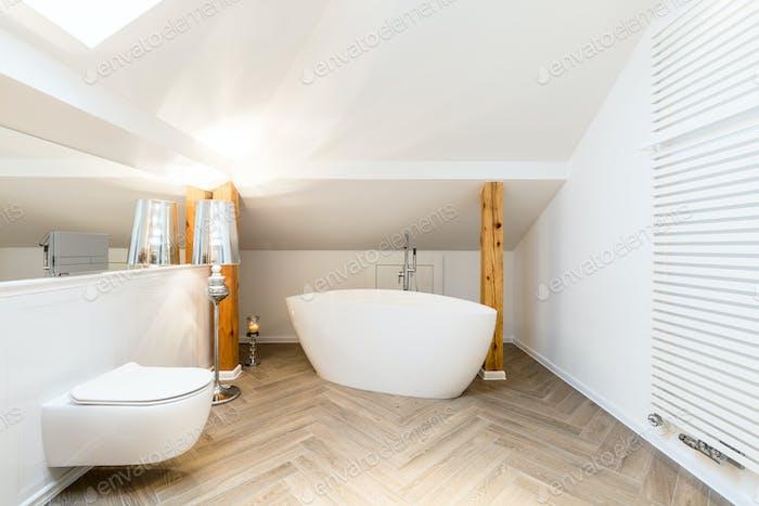 White attic bathroom with bathtub