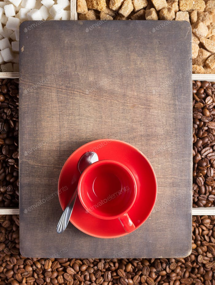 empty cup of coffee and beans on wooden tray