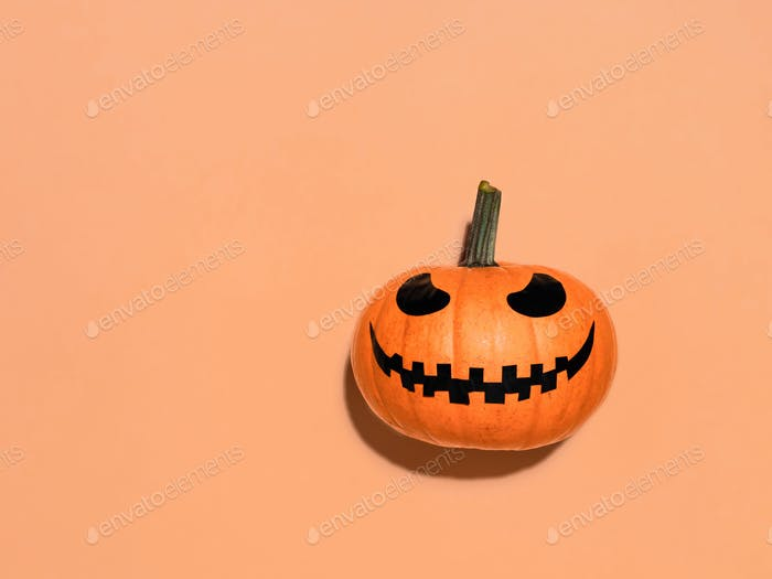 Halloween-Kürbis in der Hand auf orangefarbenem Hintergrund