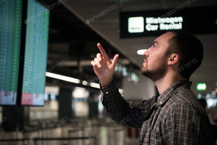 Man In Front Of Arrivals And Departures Board At The Airport. Travel concept