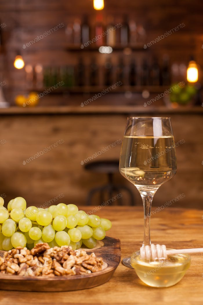 Glass of white wine with fresh grapes and wolnuts on a wooden plate in a vintage restaurant