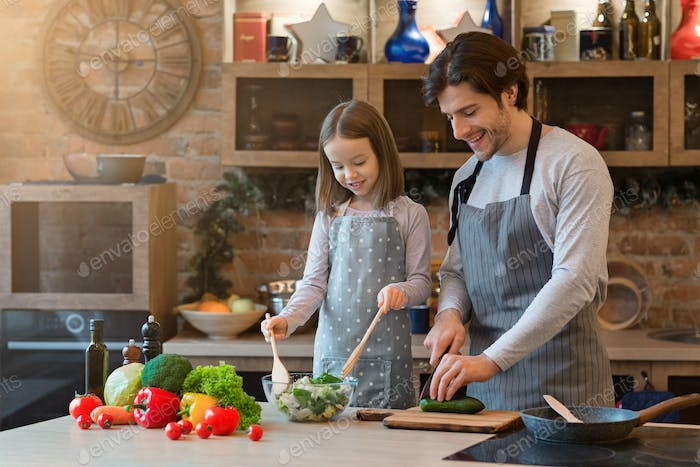 Little girl and her dad cooking healthy dinner together at home