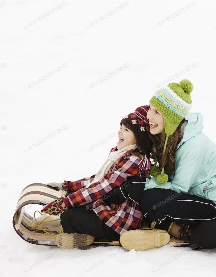 Zwei Kinder sitzen auf einem Schlitten auf dem Schnee.