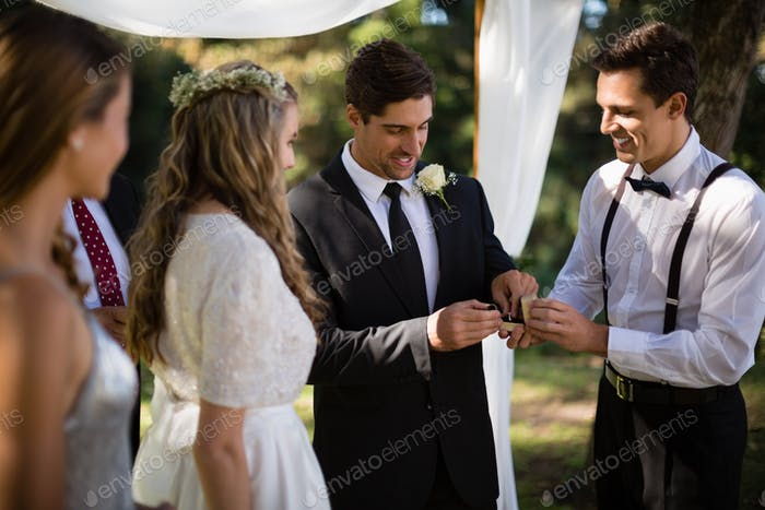 Waiter giving engagement ring to groom